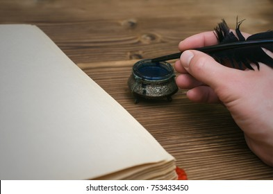 Man holding in hands feather pen and writes something in open book with blank paper page. Writer desk table. Education.