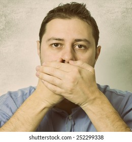 Man holding hands over his mouth