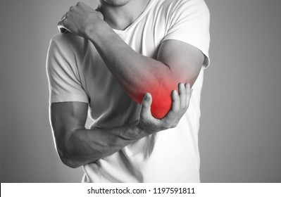 A man holding hands. Pain in the elbow. The hearth is highlighted in red. Close up. Isolated background.