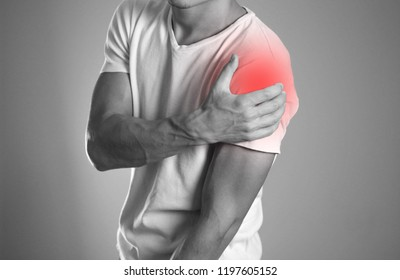 A man holding hands. Shoulder pain. The hearth is highlighted in red. Close up. Isolated background.