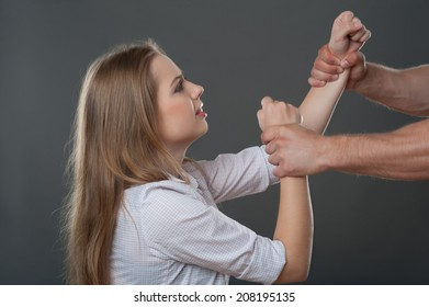 Man holding hands of very scared fair-haired woman. Isolated on grey background