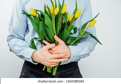 The man is holding in hands yellow tulips on a light background. The concept of handing flowers to a woman, girl. A man wearing a shirt is holding flowers in his hands.