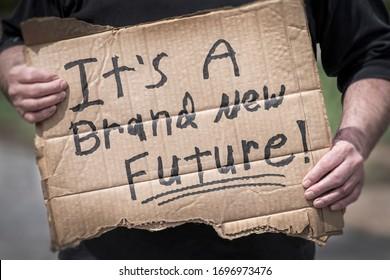 Man holding handwritten cardboard sign, It's a Brand New Future, coronavirus global pandemic, hope, change, pivot, adapt, job, employment, economy, uncertainty, positive thinking, win, victory,