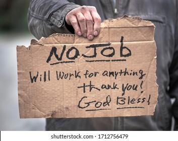 Man holding handwritten cardboard sign, No Job, Will Work, jobless, unemployed, coronavirus, employment, loss jobs, God, religion, hope, charity, giving, desperate, fired, laidoff, help, economy broke