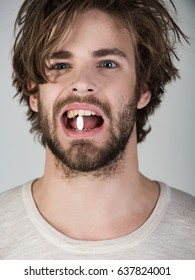 Man is holding healing pill in his teeth. White medical tablet in the mouth of sick young attractive bearded guy. Treatment and health, medicine and pharmacy concept