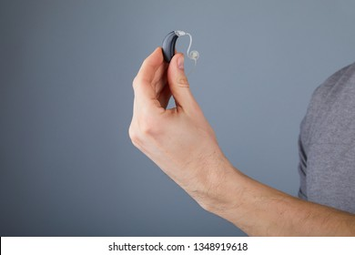 Man holding hearing aid, closeup. Hearing aids on grey background, alternative to surgery. Hearing aid device in hand, audiologist