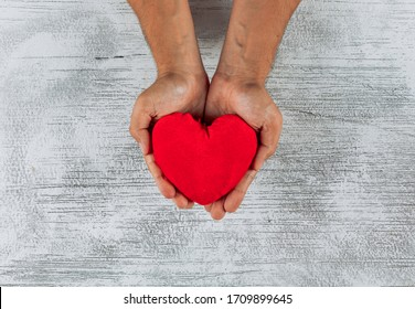 Man holding heart in his hands on a light wooden background. top view.