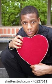 A man holding a heart shaped box