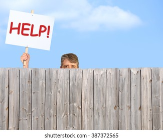 A man holding a HELP sign is peering over a fence desperate for help with his many problems in addiction, bipolar disorder, depression or could represent a man in need of anything imaginable.