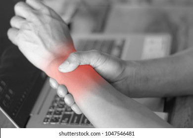 man holding her wrist pain from using computer. Office syndrome hand pain by occupational disease.