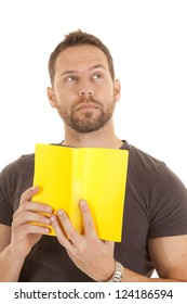 A man holding up his book with a thoughtful expression on his face.