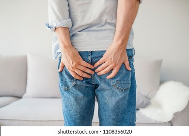 Man holding his bottom in pain, isolated in grey. Man with hemorrhoids holding his butt in pain. The pain caused by hemorrhoid.