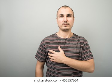 man holding his hand on his chest