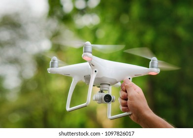 Man holding with his hand white quadcopter over green trees background. Operation of drone in air