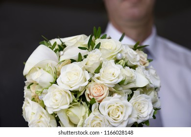 Man holding in his hand a white bridal bouquet