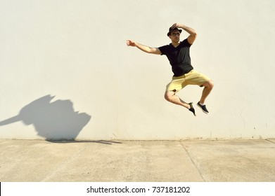 Man holding his hat and jumping in front of a wall