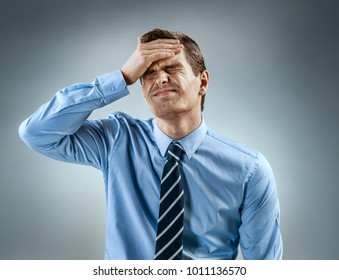 Man holding his head in pain. Photo of man in shirt and tie grimacing in pain on gray background. Medical concept