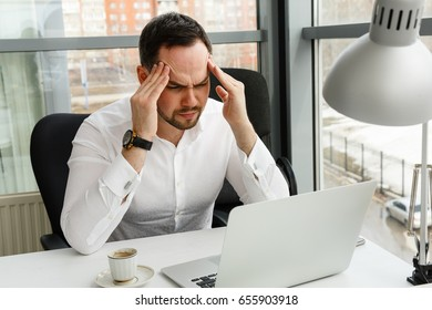 A man holding his head sitting in front of laptop