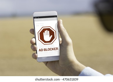 Man holding his mobile phone on the beach with ad blocker on the screen