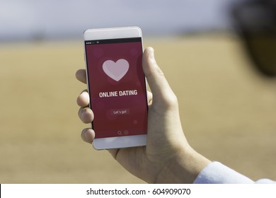 Man holding his mobile phone on the beach and using online dating app