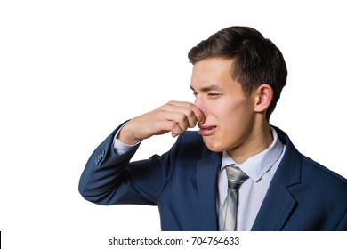 A man holding his nose because of a bad smell