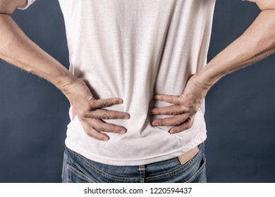 Man holding his painful inflamed loin on blue background. Health care and medicine. Suffering from back pain