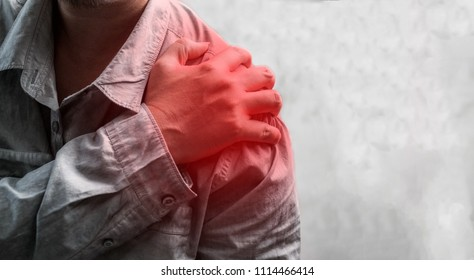 Man holding his painful shoulder, healthcare and ache in human body