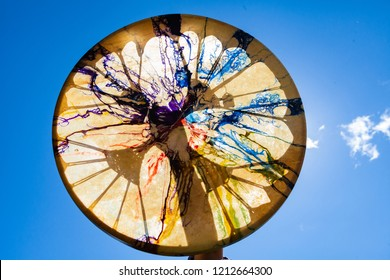 Man holding his sacred drum in the sky with sunlight going through it so that all the colors shine bright - Closeup picture with blue sky and small clouds in the background