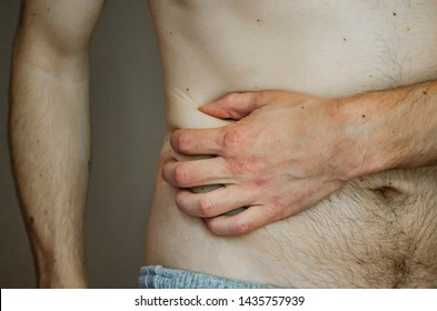 The man is holding his side. The pain in his side. Appendicitis. The concept of medicine and health. Acute pain. Close up.