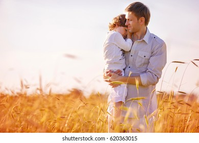A man is holding his son in his arms, standing in the middle of a wheat field. The son gently laid his head on his father's shoulder, hugging him