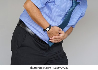 Man holding his stomach in pain on gray background. Businessman suffering from abdominal pain. Body And Health Care Concept.