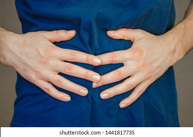 A man holding his stomach. Pain in the stomach, stomach, intestines. The concept of medicine and health. Acute pain. Close up.