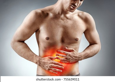 Man holding his stomach in pain. Photo of man with naked torso experience stomachaches on grey background. Medical concept