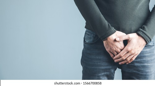 Man holding his urethra in pain on gray background