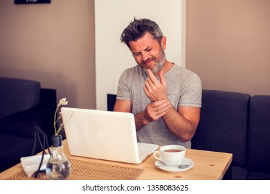 Man holding his wrist pain from using computer. Office syndrome hand pain by occupational disease. People, health care and technology concept