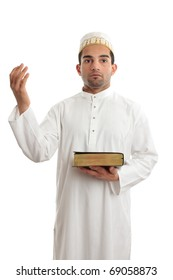 A man holding a holy book such as a bible or qur'an and hand raised in worship.  White background.