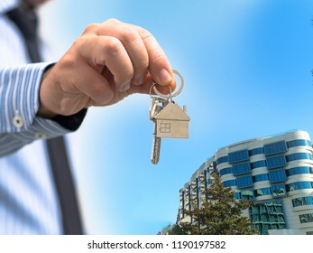 man holding a home key in his hand and residence  background