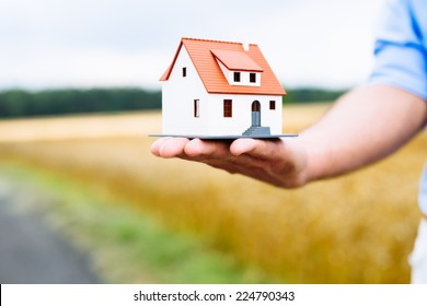 Man holding home miniature with field in background.