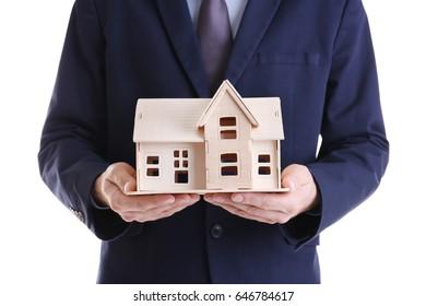 Man holding house model on white background