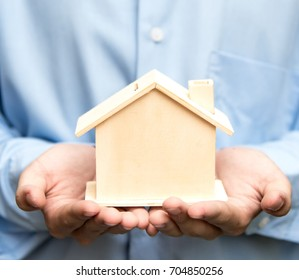 Man holding house representing home ownership and the Real Estate business.