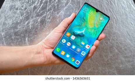 Man holding Huawei Mate 20 X smartphone in one hand on shining grey background. Display is turned on and main menu is seen Kyiv, Ukraine 15th of June 2019