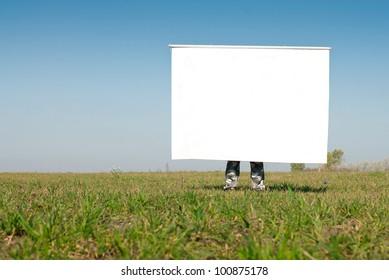 Man holding huge Sign board against blue sky