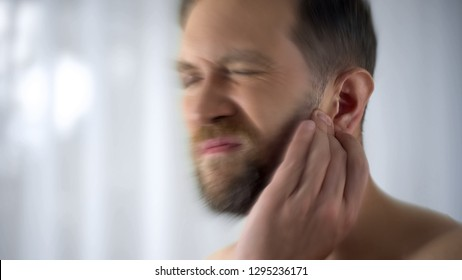 Man holding hurting ear, otitis or infection otolaryngologist problems, close up