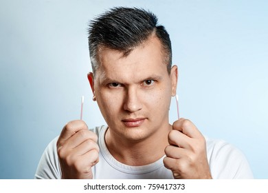 The man is holding hygienic cotton buds in his hands, close-up. The concept of body hygiene.