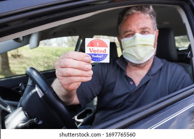 """Man holding an """"I voted today"""" sticker after voting wearing a face mask to prevent the spread of coronavirus"""
