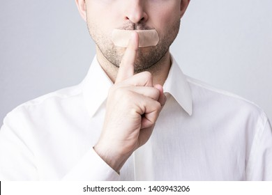 Man holding index finger at her lips, his mouth sealed with plaster, close up