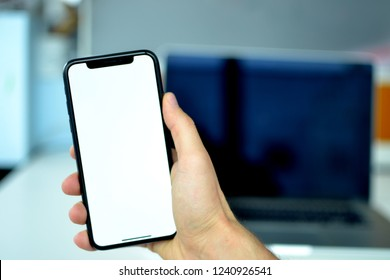 A man is holding an iPhone X in his hand and there is a MacBook Pro on the background on the office desk. The picture is shot in Istanbul, Turkey on 24/11/2018