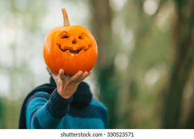 A man holding a jack o lantern carved halloween pumpkin in front of her face.