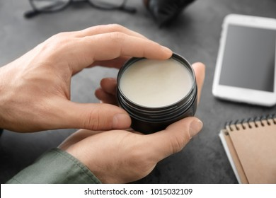 Man holding jar with clay for hair, closeup