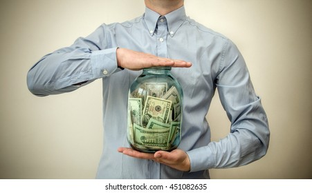 man holding a jar full of money